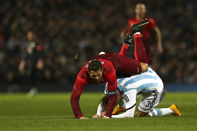 El jugador de Portugal Cristiano Ronaldo (i) disputa el balón con Cristian Ansaldi (abajo) de Argentina. Foto: EFE