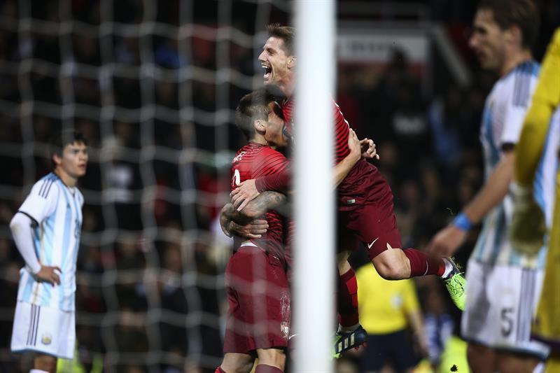 El jugador de Portugal Raphael Guerreiro (c-i) celebra con Adrien Silva (c-d) después de anotar contra Argentina. Foto: EFE