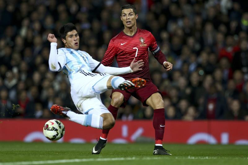 El jugador de Portugal Cristiano Ronaldo (d) disputa el balón con Facundo Roncaglia (i) Argentina. Foto: EFE