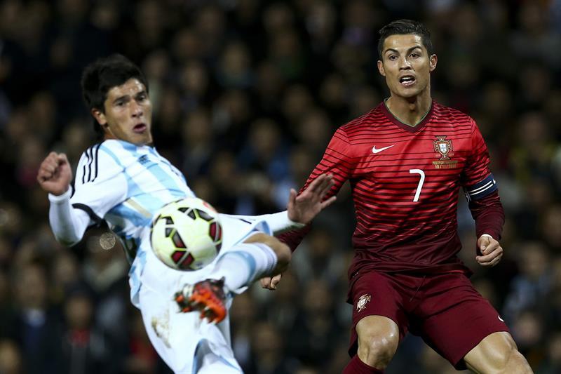 El jugador de Portugal Cristiano Ronaldo (d) disputa un balón con Facundo Roncaglia (i) de Argentina. Foto: EFE