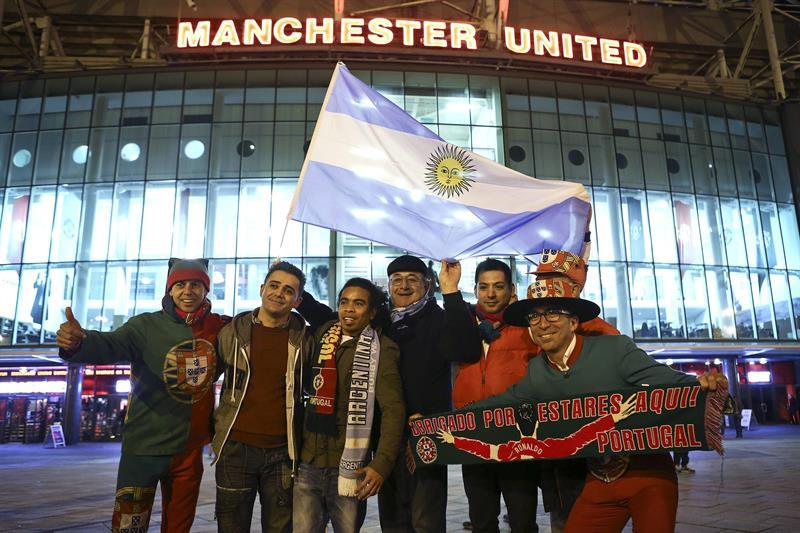 Seguidores de las selecciones de fútbol argentina y portuguesa posan frente al estadio Old Trafford. Foto: EFE