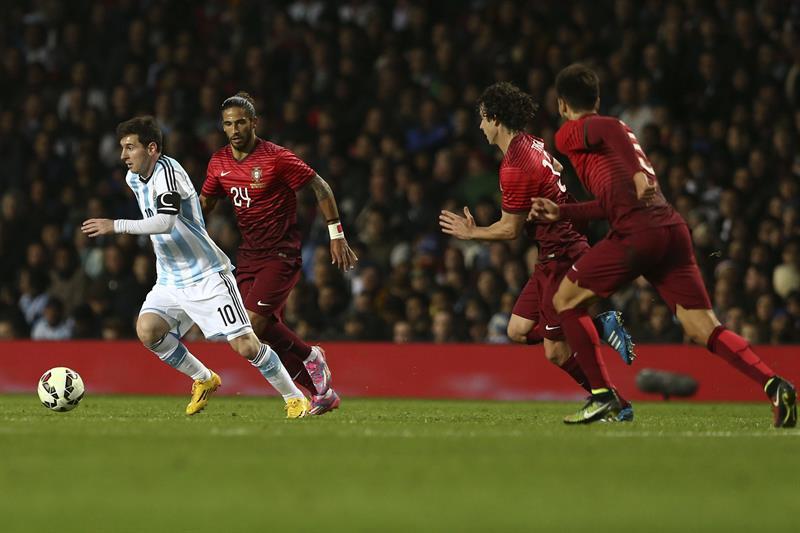 El jugador de Argentina Lionel Messi (i) avanza con el balón ante Portugal. Foto: EFE