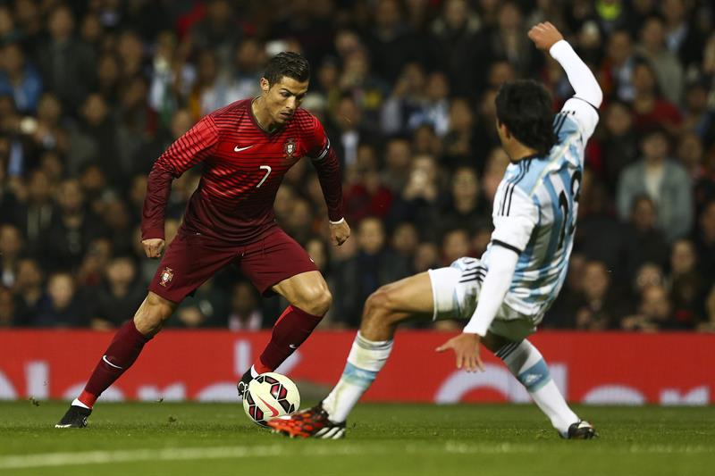 El jugador de Portugal Cristiano Ronaldo disputa el balón con Facundo Roncaglia (d) Argentina. Foto: EFE