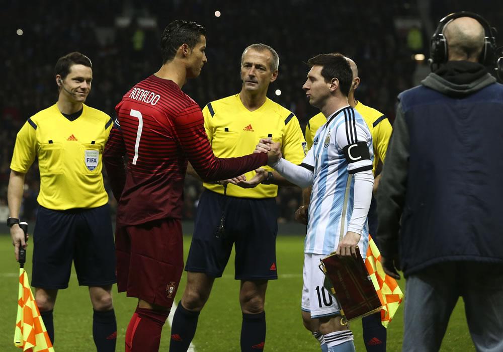 El jugador de Portugal Cristiano Ronaldo (2-i) y Lionel Messi de Argentina (2-d) se saludan antes del amistoso en el estadio Old Trafford. Foto: EFE