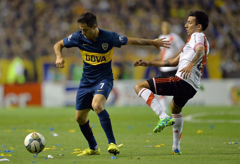 uan Manuel Martinez(i) de Boca Juniors disputa la pelota Leonel Vangioni(d) de River Plate. EFE