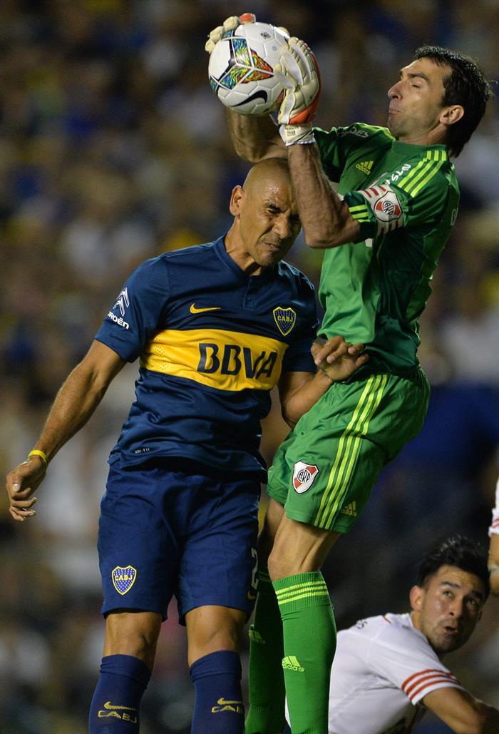 Daniel Diaz(i) de Boca Junior salta a disputar un balón con Marcelo Barovero (d) de River Plate. EFE