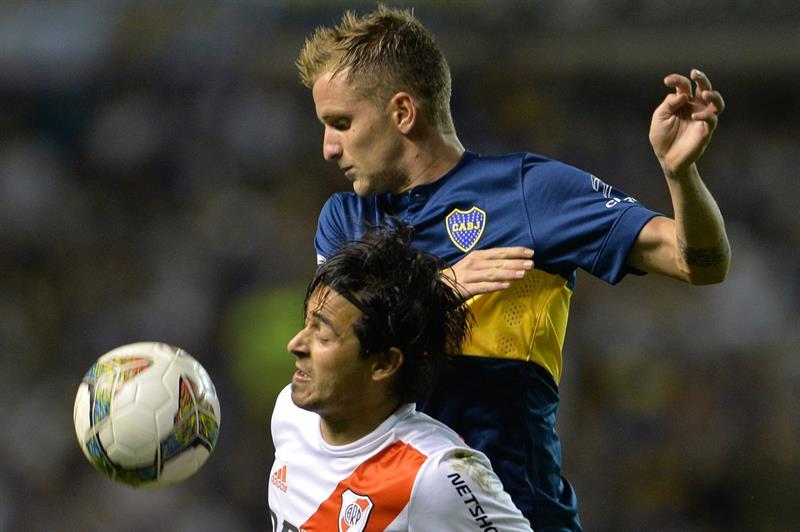 Nicolas Colazo(arriba) de Boca Juniors disputa la pelota Leonardo Pisculichi(abajo) de River Plate. EFE
