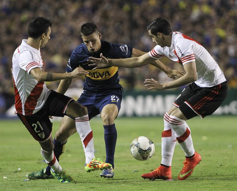 El jugador Jonathan Calleri (c) de Boca Juniors disputa el balón con el jugador Leonel Vangioni (i) y Gabriel Mercado (d) de River Plate. EFE