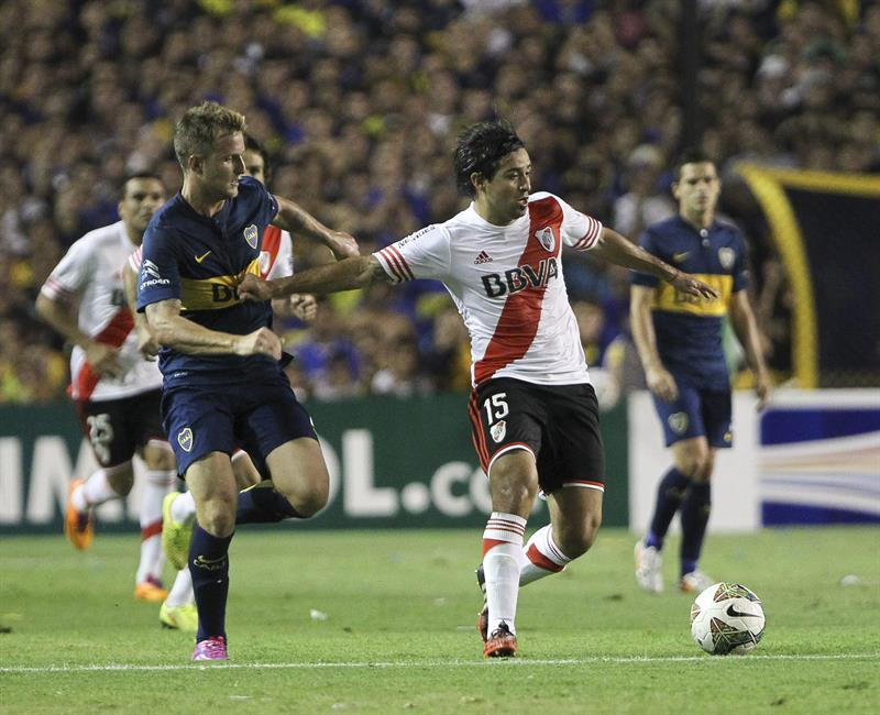 El jugador Nicolas Colazo de Boca Juniors disputa el balón con el jugador Leonardo Pisculichi (d) de River Plate. EFE