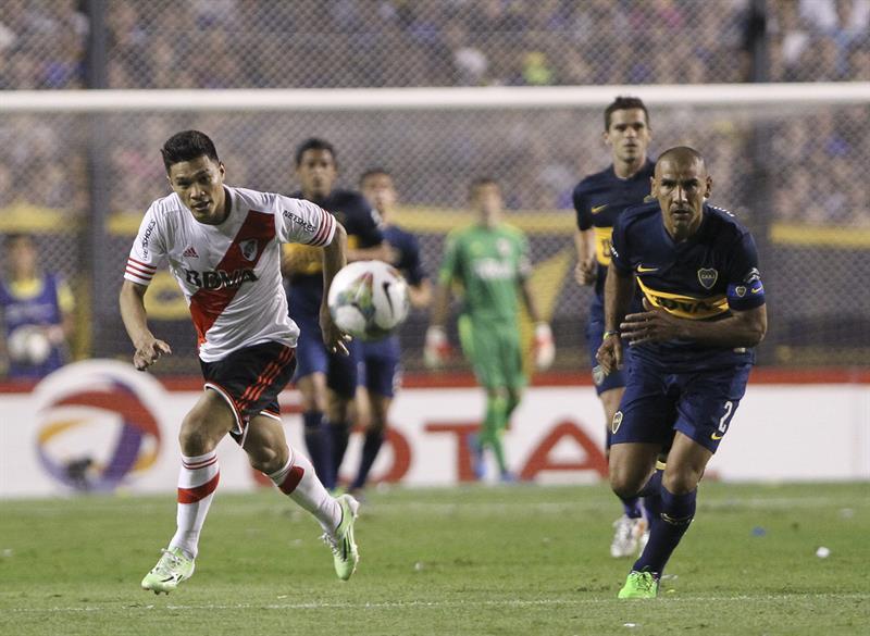 El jugador Daniel Díaz de Boca Juniors disputa el balón con el jugador colombiano Teofilo Gutiérrez (i) de River Plate. EFE
