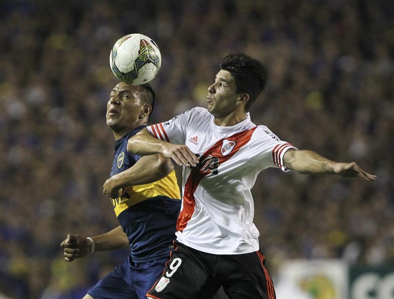 El jugador Andres Chavez (i) de Boca Juniors disputa el balón con el jugador Giovanni Simeone de River Plate. EFE