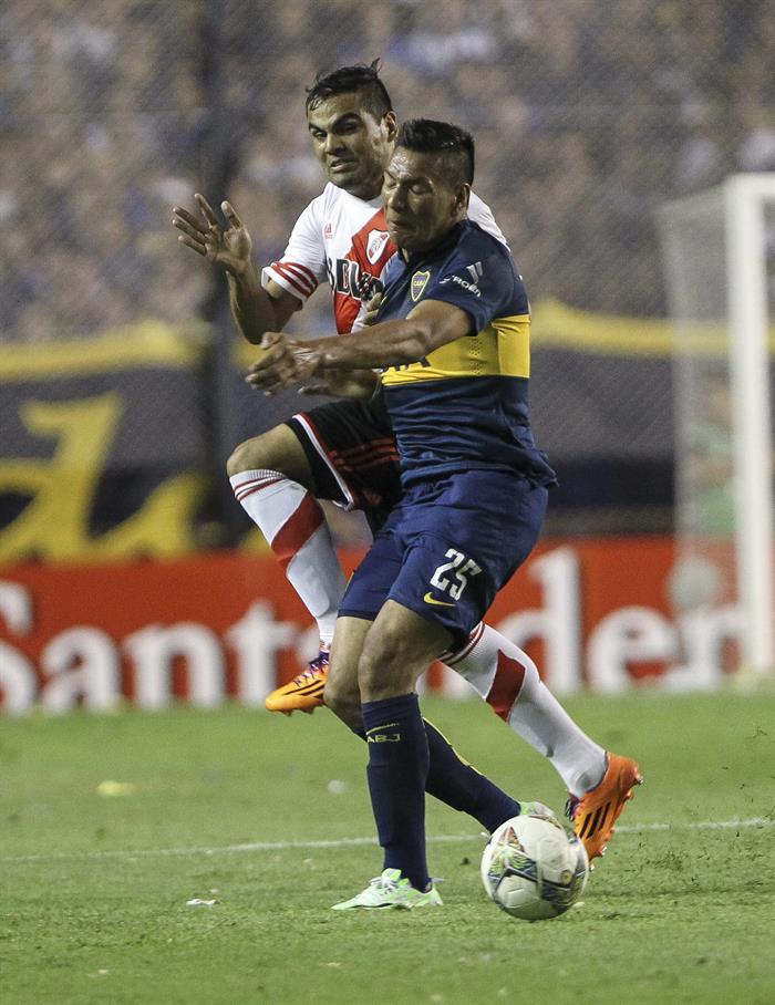 El jugador Andres Chavez de Boca Juniors disputa el balón con el jugador Gabriel Mercado (atrás) de River Plate. EFE