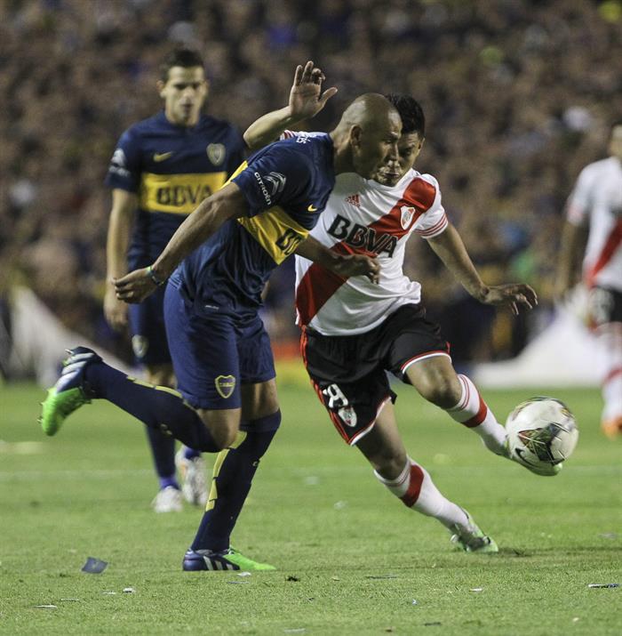 El jugador Daniel Diaz de Boca Juniors disputa el balón con el jugador colombiano Teofilo Gutiérrez (d) de River Plate. EFE
