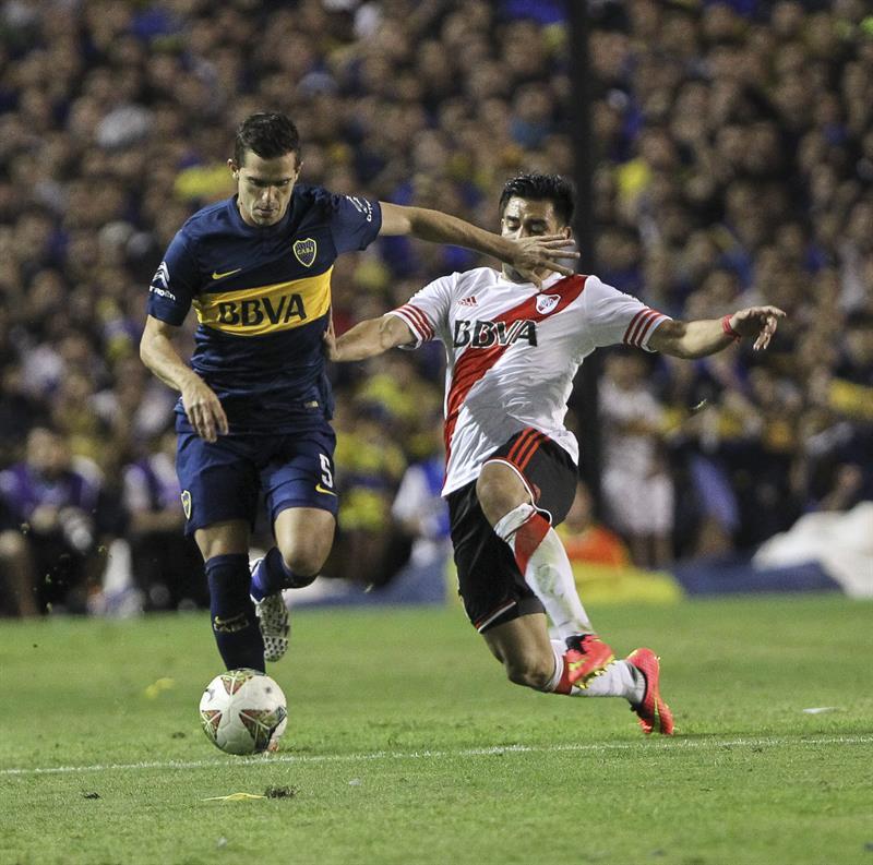 El jugador Fernando Gago de Boca Juniors disputa el balón con el jugador Leonel Vangioni (d) de River Plate. EFE