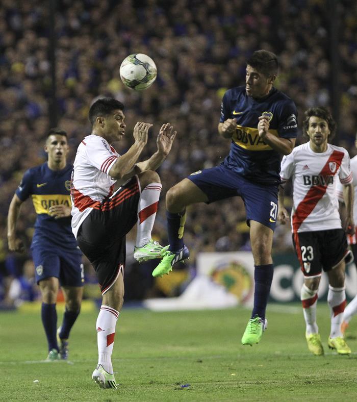 El jugador Cristian Erbes de Boca Juniors disputa el balón con el jugador Gabriel Mercado de River Plate. EFE