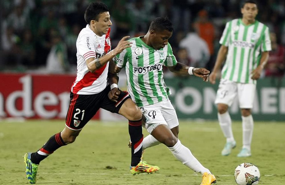 El jugador de Atlético Nacional Wilder Guisao (d) disputa un balón con Leonel Vangioni (i) de River Plate. Foto: EFE