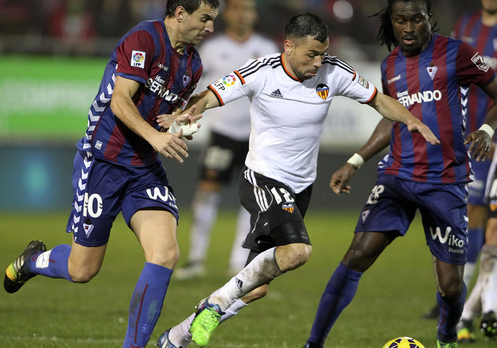 El jugador argentino del Valencia Piatti (c) trata de escapar entre Arruabarrena (i) y Boateng, ambos del Eibar. Foto: EFE