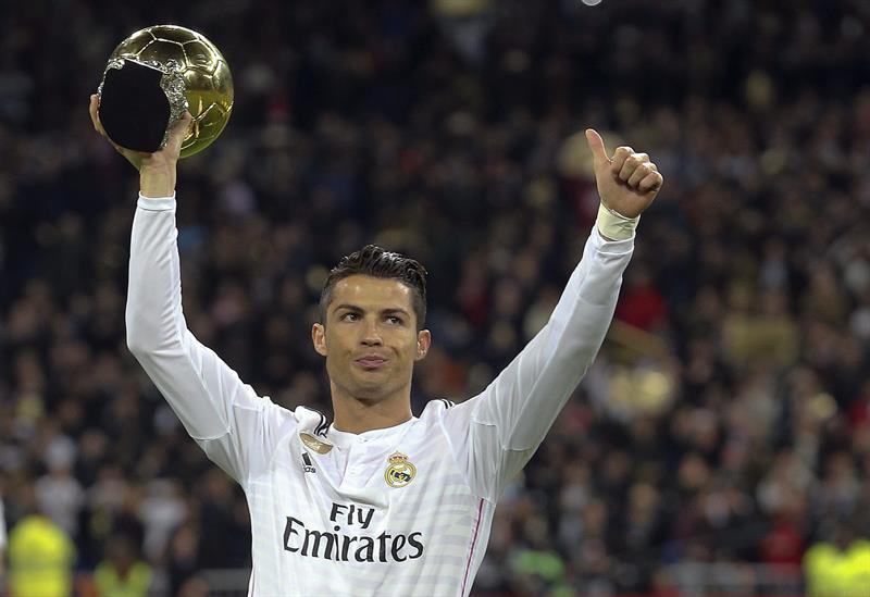 El delantero portugués del Real Madrid Cristiano Ronaldo ofrece su tercer balón de oro que ha logrado, a la afición antes del partido de vuelta de octavos de final. EFE