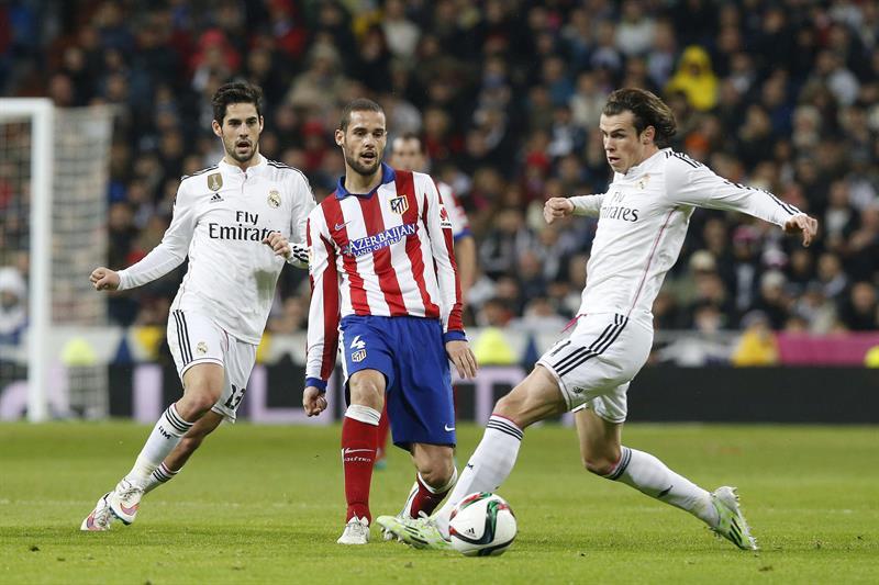 El delantero galés del Real Madrid Gareth Bale (d) controla el balón ante el centrocampista del Atlético de Madrid Mario Suárez (c), y su compañero Francisco Román Alarcón. EFE