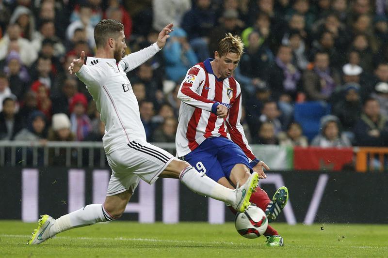 El delantero del Atlético de Madrid Fernando Torres (d) dispara ante el defensa del Real Madrid Sergio Ramos. EFE