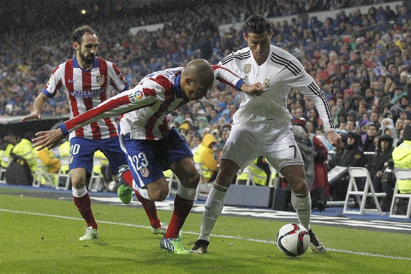 El delantero portugués del Real Madrid Cristiano Ronaldo (d) lucha un balón con el defensa brasileño del Atlético de Madrid Joao Miranda. EFE