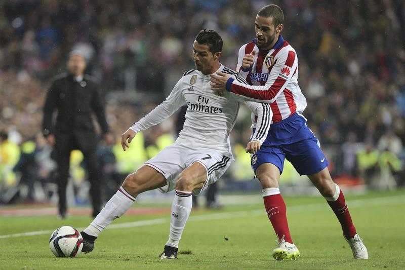 El delantero portugués del Real Madrid Cristiano Ronaldo (i) con el balón ante el defensa del Atlético de Madrid Mario Suárez. EFE