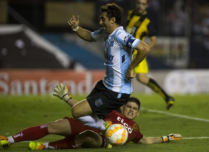 El jugador de Racing Club de Argentina Diego Milito (arriba) disputa el balón con el portero Alfredo Aguilar de Guaraní de Paraguay. EFE
