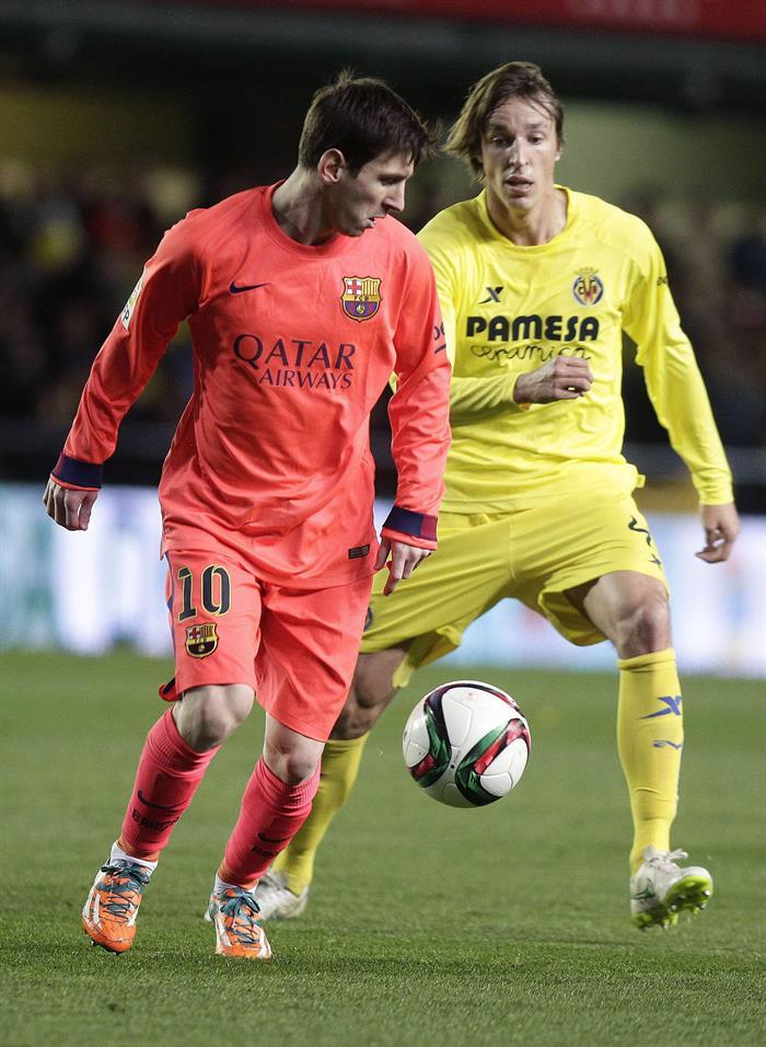 El delantero argentino del FC Barcelona Leo Messi (i) pelea un balón con Tomás Pina, centrocampista del Villarreal. EFE