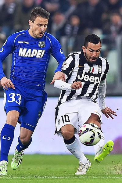 El jugador del Juventus Carlos Tevez (d) disputa el balón ante Matteo Brighi (i) del Sassuolo. Foto: EFE