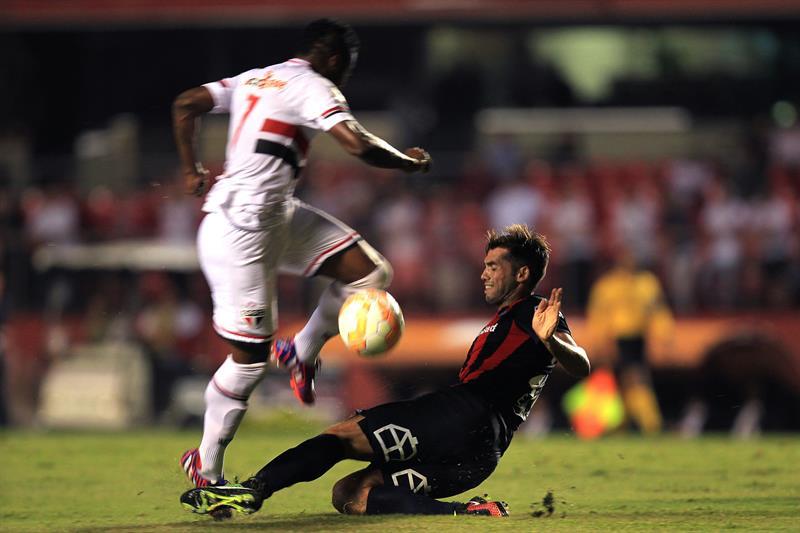 El jugador de Sao Paulo brasileño Michel Bastos (i) disputa el balón con Emmanuel Mas (d) de San Lorenzo. EFE