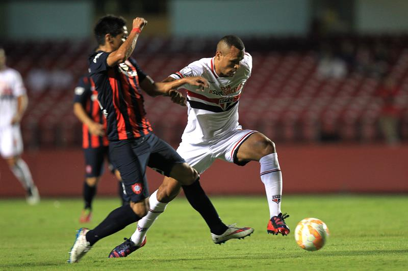 El jugador de Sao Paulo brasileño Luis Fabiano (d) disputa el balón con Pablo Barrientos (i) de San Lorenzo. EFE