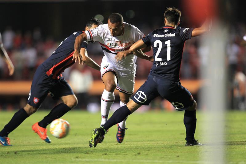 El jugador de Sao Paulo brasileño Luis Fabiano (c) disputa el balón con Mario Alberto Yepes (i) y Emmanuel Mas (d) de San Lorenzo. EFE
