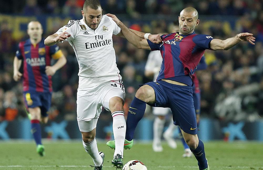 El delantero francés del Real Madrid, Karim Benzema (i), disputa un balón con el defensa argentino del F. C. Barcelona, Javier Mascherano. Foto: EFE