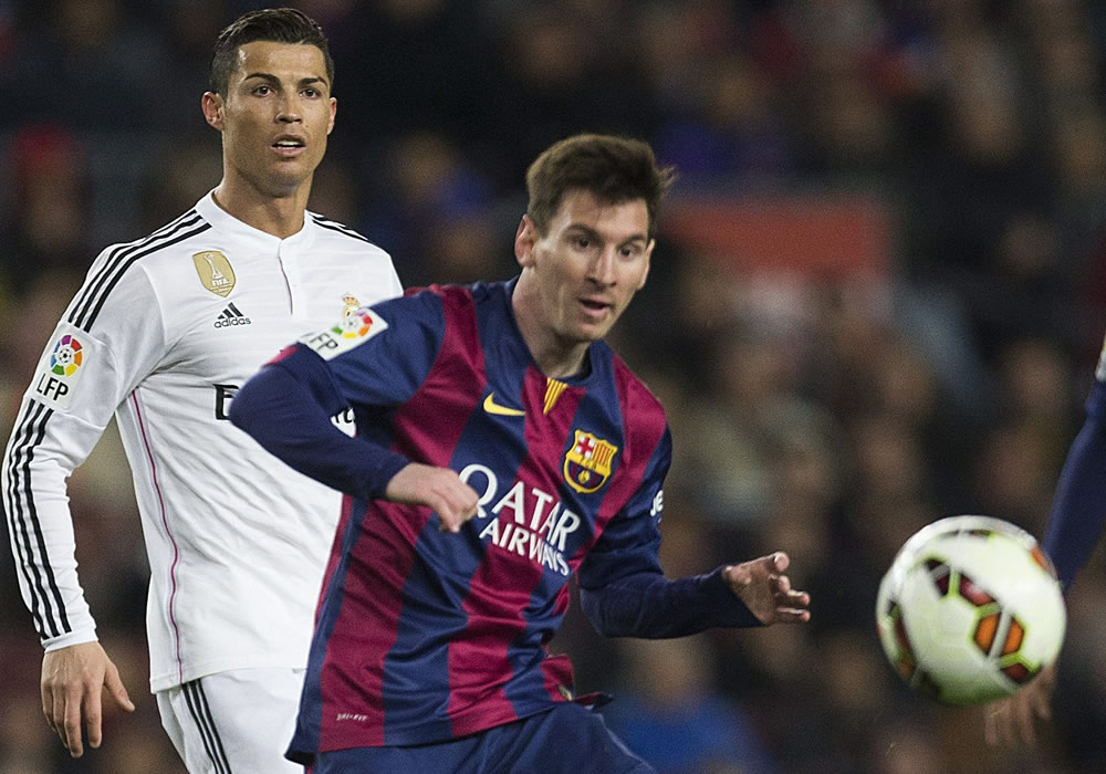 El delantero argentino del FC Barcelona Leo Messi (d) centra el balón junto al portugués Cristiano Ronaldo (i), del Real Madrid. Foto: EFE