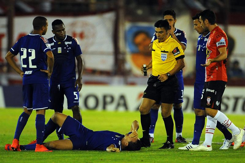 El jugador de Cruzeiro de Brasil Leandro Damiao (abajo) se lamenta tras una falta de Huracán de Argentina. EFE