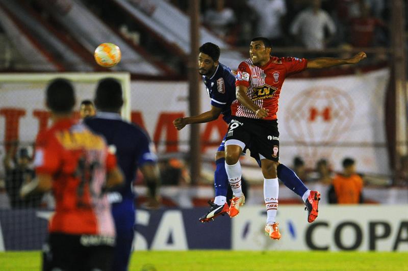 El jugador de Huracán de Argentina Ramon Abila (i) disputa el balón con Leo (c) de Cruzeiro de Brasil. EFE
