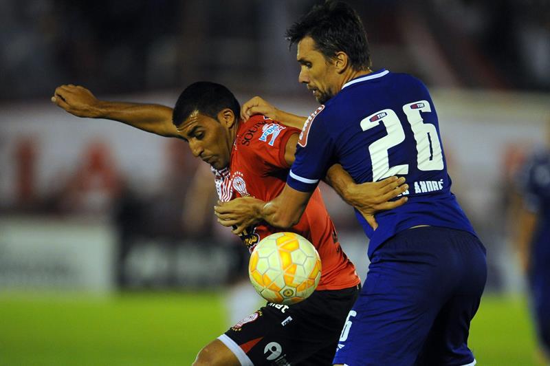 El jugador de Huracán de Argentina Ramon Abila (i) disputa el balón con jugador Paulo Andre (d) de Cruzeiro. EFE