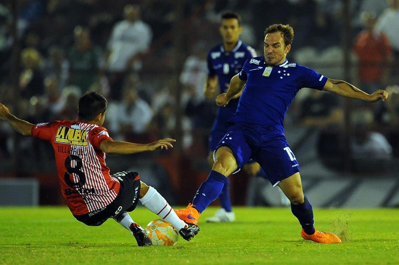 El jugador de Huracan de Argentina Lucas Villarruel (i) disputa el balón con jugador Willians Farias(d) de Cruzeiro. EFE