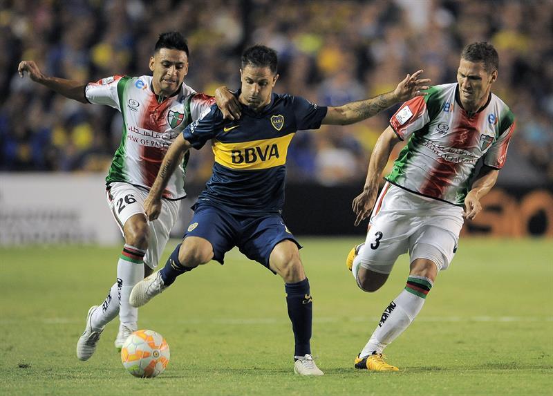 Juan Manuel Martinez(c) de Boca Juniors disputa la pelota con German Lanaro y Diego Torres de Palestino de Chile. EFE