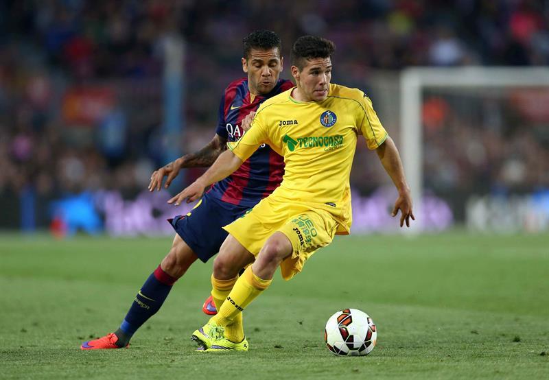 El defensa del FC Barcelona Dani Alves (i) lucha el balón con el delantero argentino del Getafe Emi Buendia. Foto: EFE