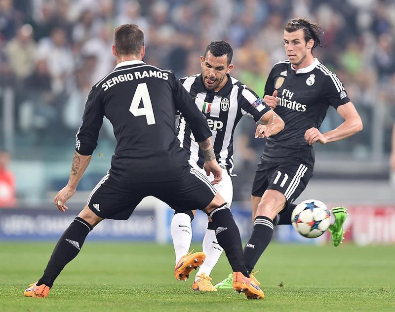 El jugador de Juventus Carlos Tevez (c) patea el balón ante la marca de Sergio Ramos. EFE