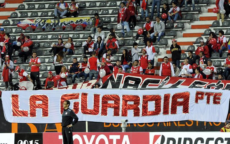 Hinchas de Independiente Santa Fe animan a su equipo ante Estudiantes. EFE