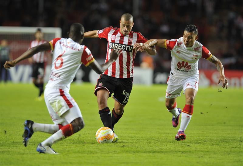 Matías Aguirregaray (c) de Estudiantes ante Luis Carlos Arias (d) y Dairon Mosquera (i) de Independiente Santa Fe. EFE