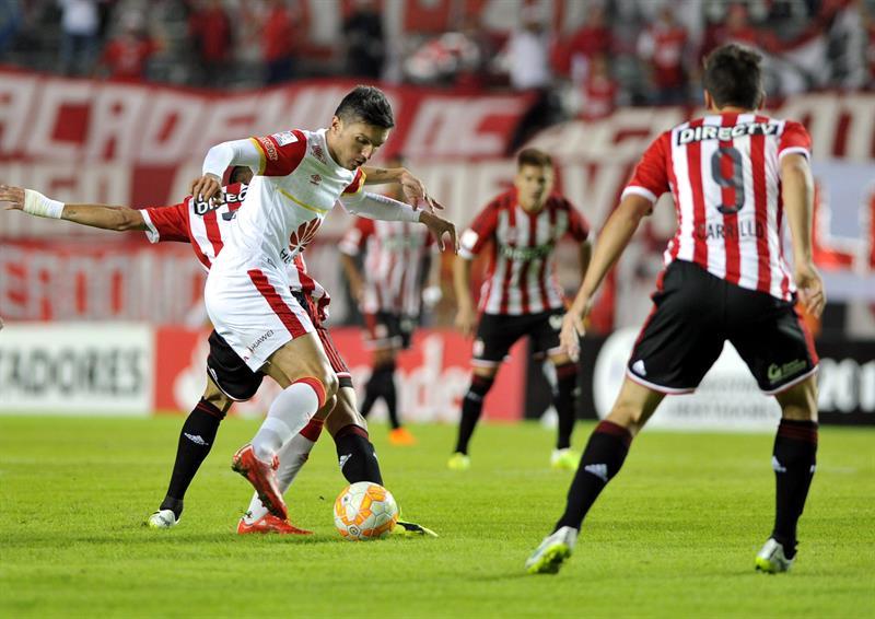Carlos Auzqui (atrás) y Guido Carrillo (d) de Estudiantes ante Juan Daniel Roa (i) de Independiente Santa Fe. EFE