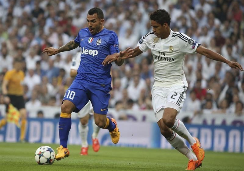 El defensa francés del Real Madrid Raphael Varane (d) lucha el balón con el argentino Carlos Tévez. Foto: EFE