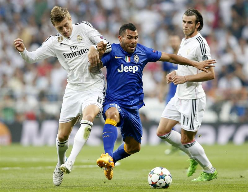 El delantero argentino de la Juventus Carlos Tévez (c) lucha el balón con el alemán Toni Kroos (i), del Real Madrid. Foto: EFE