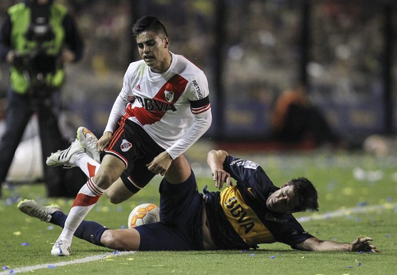 Pablo Pérez de Boca Juniors disputa el balón con Gonzalo Martínez de River Plate. EFE