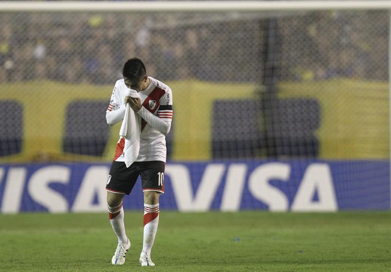 Gonzalo Martínez de River Plate se limpia el rostro luego de que lanzaran gas pimienta desde la tribuna. Foto: EFE