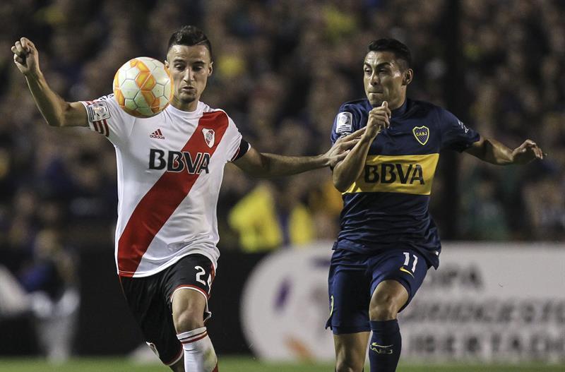 El jugador Federico Carrizo (d) de Boca Juniors disputa el balón con Emanuel Mammana (i) de River Plate. Foto: EFE