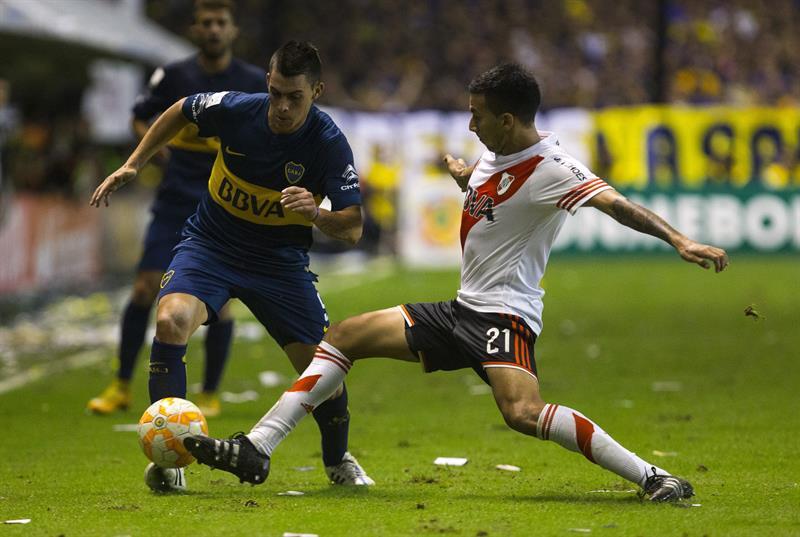 Cristian Pavón (i) de Boca Juniors disputa el balón con Leonel Vangioni de River Plate. Foto: EFE